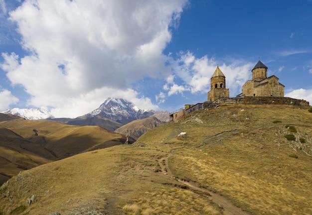 Schöne ansicht der dreifaltigkeitskirche von gergeti gefangen unter dem bewölkten himmel in georgia