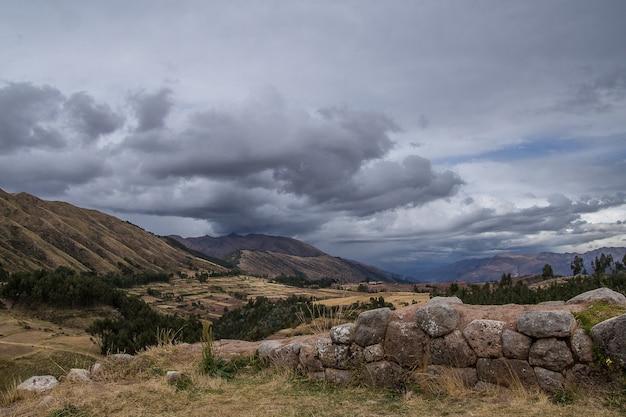 Schöne ansicht der felder auf den bergen unter dem bewölkten himmel gefangen in cusco, peru