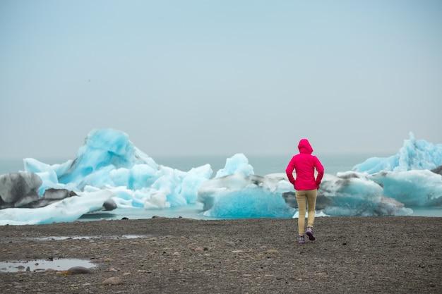 Schöne ansicht der frau entspannen sich in der sommerzeit, eisberge in jokulsarlon-gletscherlagune