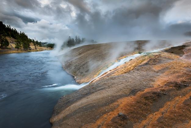 Schöne ansicht der landschaft in yellowstone während heiße quelle, die zum fluss fließt.