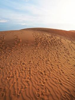 Schöne ansicht der roten sanddünen mit fußabdruckbeschaffenheitshintergrund.
