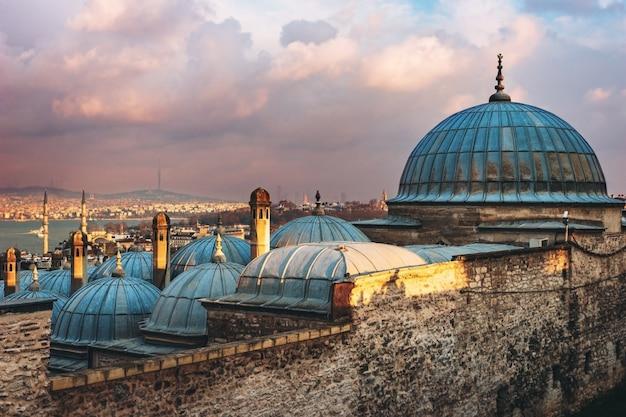 Schöne ansicht des goldenen horns bei sonnenuntergang, istanbul, die türkei. die dächer der süleymaniye-moschee in den strahlen der untergehenden sonne gegen das blaue meer in istanbul