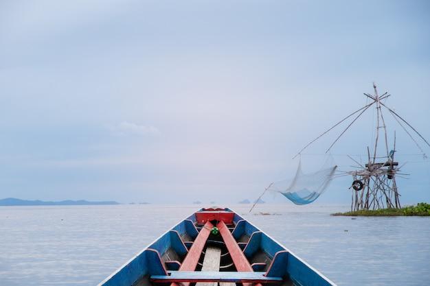 Schöne ansicht des hölzernen bootes auf landschaftlich reizvollem im see mit großem netzaufzug der dorfbewohner bei phatthalung provinzen thailand.