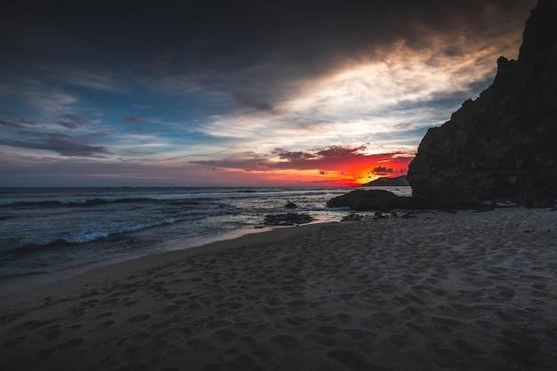 Schöne ansicht des strandes und des welligen ozeans bei sonnenuntergang in lombok, indonesien gefangen genommen