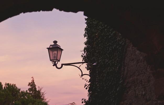 Schöne ansicht einer blatt bedeckten steinmauer und einer straßenlaterne unter dem bunten himmel