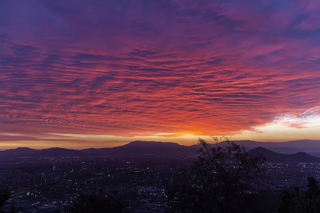 Schöne ansicht einer stadt in einem tal unter dem exotischen bunten himmel