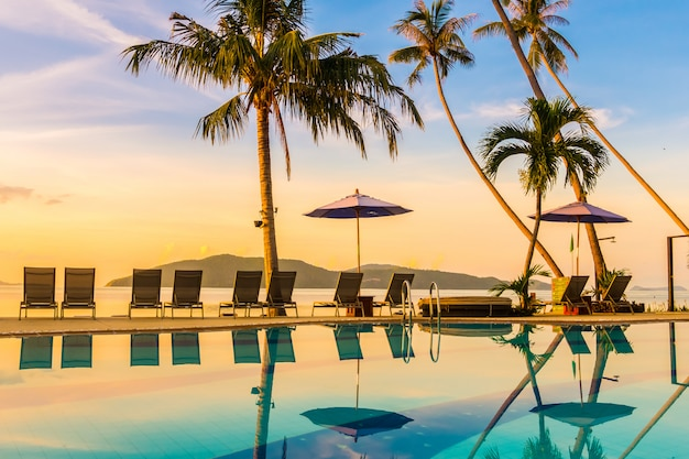 Schöne ansicht im freien mit regenschirm und stuhl um swimmingpool im luxushotel