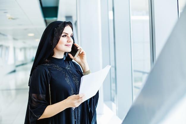 Schöne arabische frau, die abaya trägt, die über telefon spricht