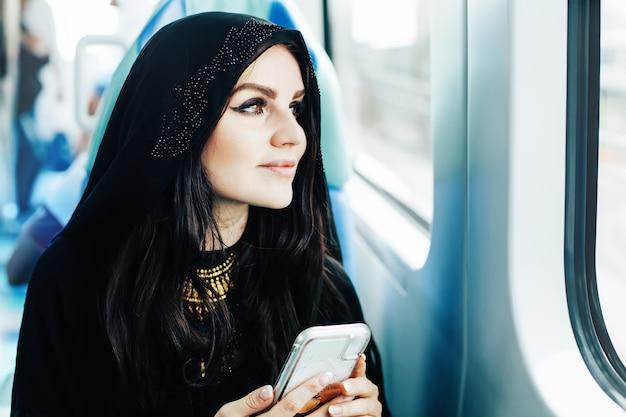 Schöne arabische frau im hijab, die in öffentlichen verkehrsmitteln pendelt