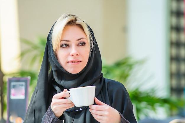 Schöne arabische frau in einem restaurant, das einen kaffee trinkt. arabischer modestil. nahöstliche frau, die in einem restaurant sitzt, das hijab und abaya trägt. frühstück