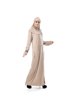 Schöne arabische frau posiert im stilvollen hijab isoliert auf studiohintergrund. modekonzept