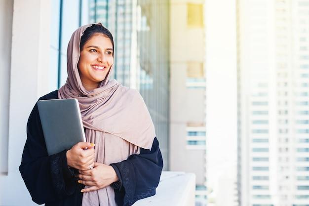 Schöne arabische muslimische junge frau im hijab mit laptop in einer stadt
