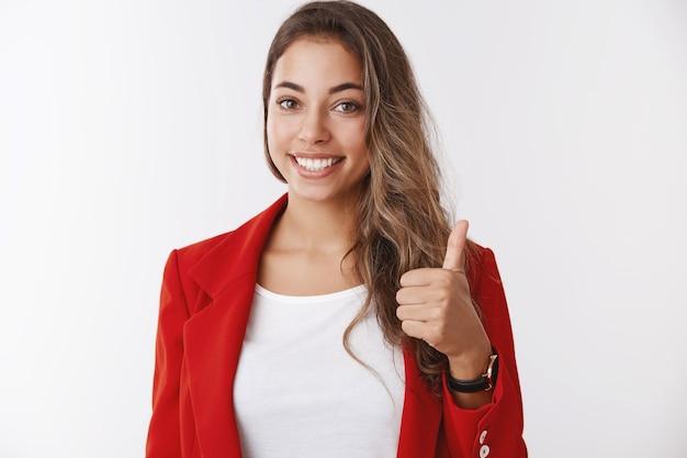 Schöne arbeit, stolz sie. porträt unterstützendes weibliches teammitglied, das daumen hoch zeigt, zustimmend lächelt, zustimmend, beeindruckt von der großartigen anstrengung der mitarbeiter, stehend zufriedene weiße wand