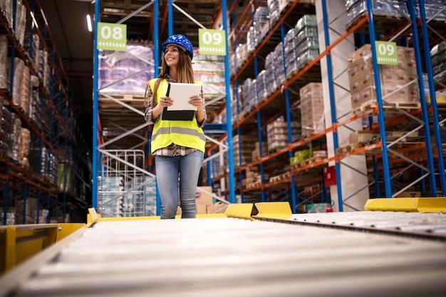 Schöne arbeiterin mit helm und checkliste, die verteilung im lagerzentrum steuert