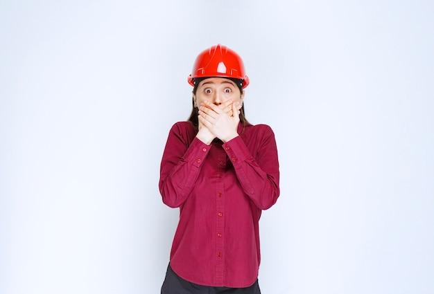 Schöne architektin im roten helm, die ihren mund steht und bedeckt.