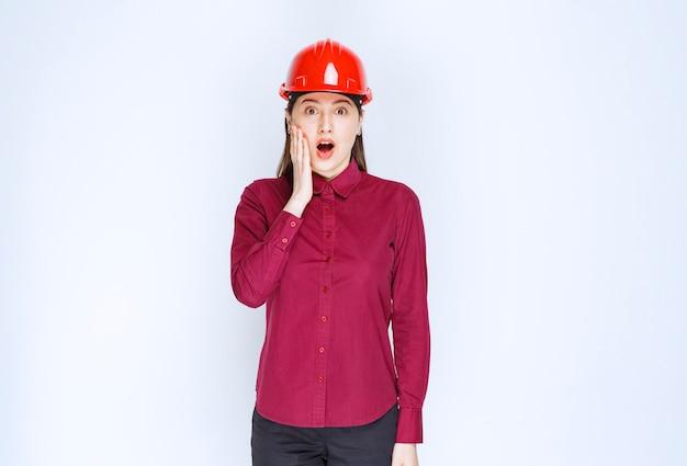 Schöne architektin im roten helm überrascht von etwas.