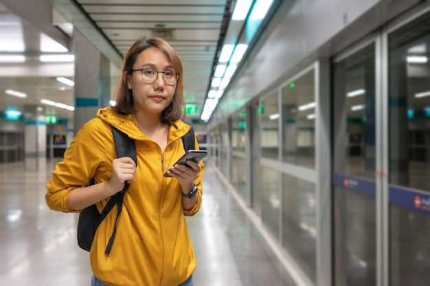 Schöne asiatin des porträts, die einen smartphone halten wartet auf die u-bahn steht