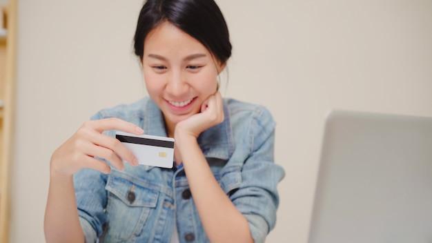 Schöne asiatin, die den laptop kaufen online kaufen mit kreditkarte verwendet, während das zufällige sitzen auf schreibtisch im wohnzimmer zu hause sitzt.