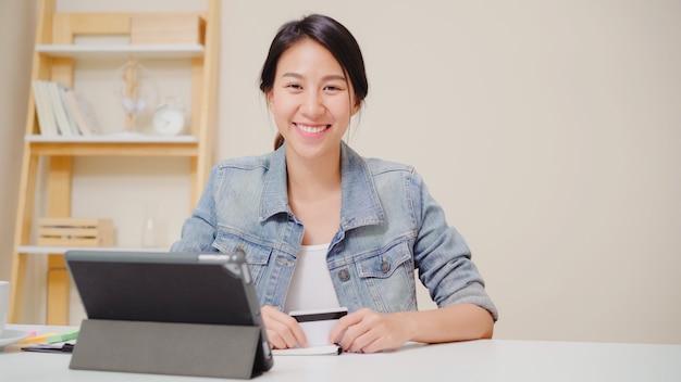 Schöne asiatin, die die tablette kaufen online kaufen mit kreditkarte beim zufälligen sitzen der abnutzung auf schreibtisch im wohnzimmer zu hause verwendet.