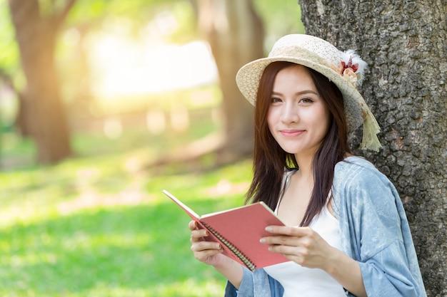Schöne asiatin, die rosa buch im parkliebesspeicher oder -tagebuch liest