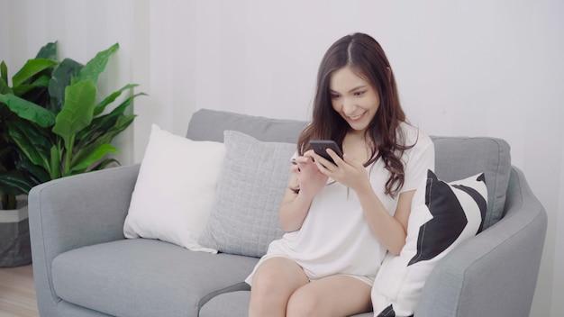 Schöne asiatin, die smartphone beim lügen auf der couch in ihrem wohnzimmer verwendet.