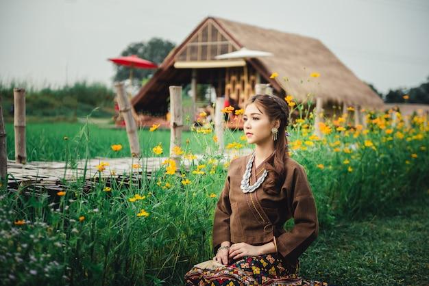 Schöne asiatin im lokalen kleid, das auf dem boden sitzt und genießen natürlich auf dem reisgebiet