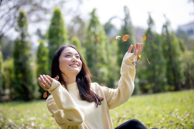 Schöne asiatin lächelndes glückliches mädchen und tragen des warmen kleidungswinter- und -herbstportraits an outd