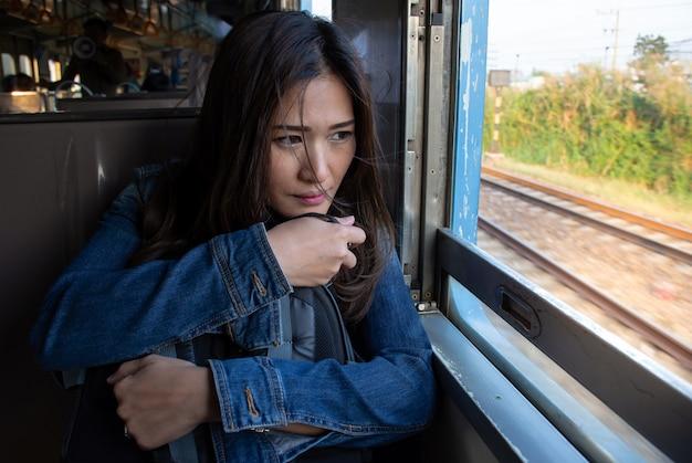 Schöne asiatinreise mit dem zug, der nahe dem fenster sitzt und durch das zugfenster schaut.
