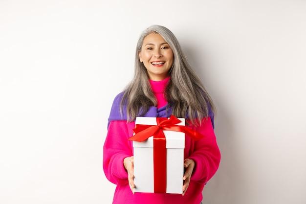 Schöne asiatische ältere frau, die lächelt, mit valentinstag gratuliert, geschenk im kasten hält und über weißem hintergrund steht.