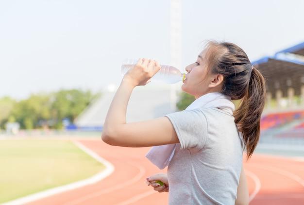 Schöne asiatische athletenfrau, die wasser von der flasche trinkt
