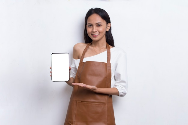 Schöne asiatische barista-kellnerin, die handy auf weißem hintergrund demonstriert