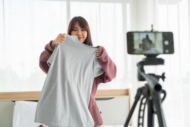 Schöne asiatische bloggerin, die kleidung vor der kamera zeigt, um vlog video aufzuzeichnen