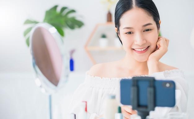 Schöne asiatische bloggerin zeigt, wie man kosmetik herstellt und verwendet.