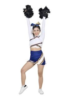 Schöne asiatische cheerleaderin mit den händen in der luft mit pompons