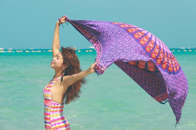Schöne asiatische dame, die mit stranddecke spielt