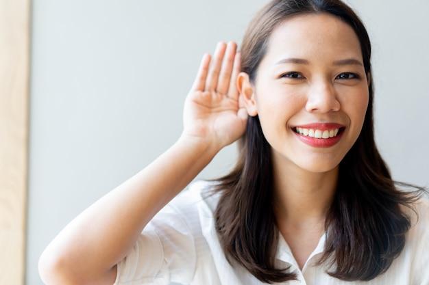 Schöne asiatische doktorfrau, die hand hinter ohr lächelt und verwendet, um zu versuchen, auf taubheitskonzept zu hören