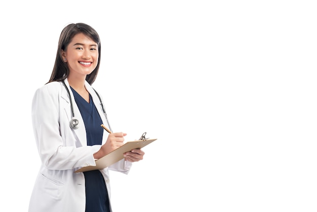 Schöne asiatische doktorfrau mit laborkittelschreibensanmerkungen über das klemmbrett