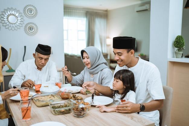 Schöne asiatische familie, die ihr iftar abendessen zu hause genießt. ramadan kareem islam brechen fasten tradition