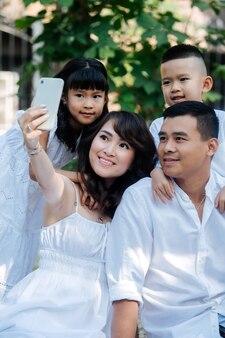 Schöne asiatische familie in weißer kleidung, die selfie in einem park macht. sie machen ein picknick und genießen die letzten warmen tage des frühen herbstes. eltern und ihre kinder in einem baumschatten.