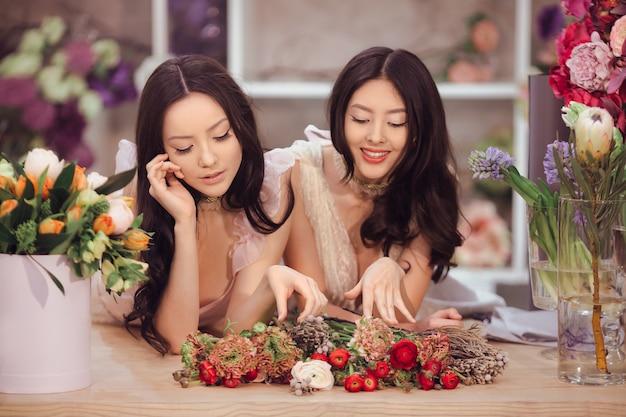 Schöne asiatische floristenmädchen, die blumenstrauß auf tisch zum verkauf gegen blumenbokeh machen