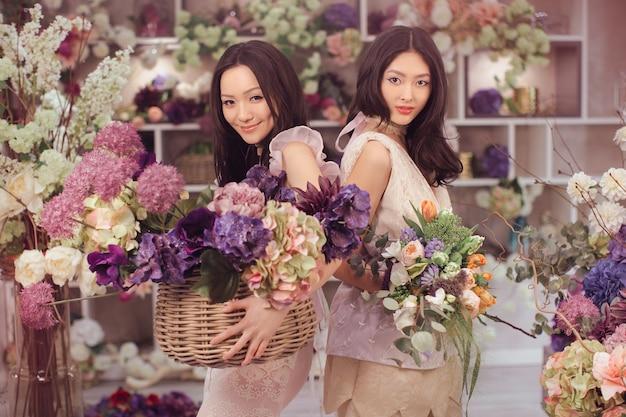 Schöne asiatische floristenmädchen, die blumenstrauß und blumenkorb für verkauf gegen blumenbokeh halten