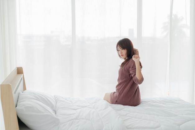 Schöne asiatische frau auf dem bett und am morgen aufwachend