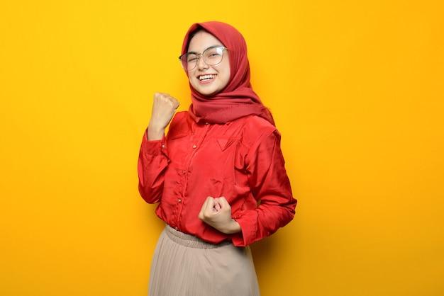 Schöne asiatische frau aufgeregt auf gelbem hintergrund