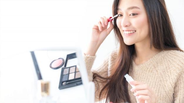 Schöne asiatische frau blogger zeigt, wie man kosmetik bildet und verwendet