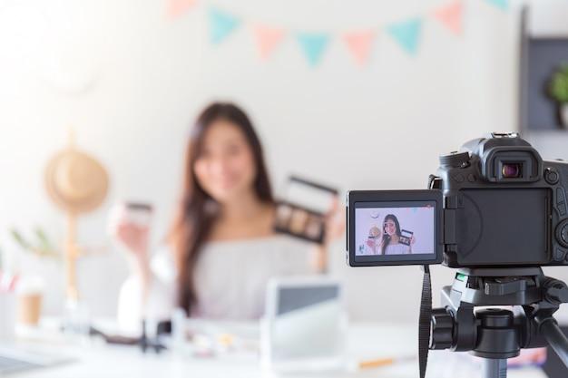 Schöne asiatische frau blogger zeigt, wie man kosmetik bildet und verwendet.