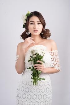 Schöne asiatische frau braut auf grauem hintergrund. nahaufnahmeportraits mit professionellem make-up