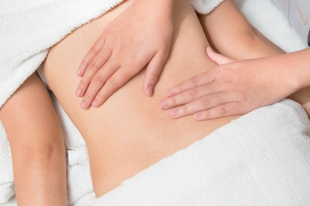 Schöne asiatische frau der nahaufnahme, die viszerale massage hat