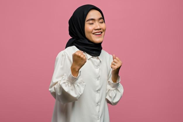 Schöne asiatische frau des glücks, die ein weißes hemd mit erfolgreichem ausdruck trägt
