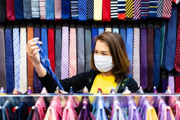 Schöne asiatische frau des mittelalters, die eine bunte krawatte im geschäft hält und wählt
