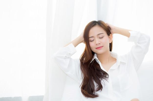 Schöne asiatische frau des porträts, die das fenster steht